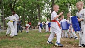 Dzieci angażują w sportach, karate outdoors, trener wydają instrukcj batalistyczne dziewczyny i chłopiec w kimonie, sztuki samoob zbiory wideo
