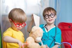 Dzieci bawić się doktorski indoors i leczyć mokiet zabawkę obraz stock