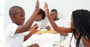 Dzieci bawić się na łóżku podczas gdy rodzice ma śniadanie na łóżku zdjęcie wideo