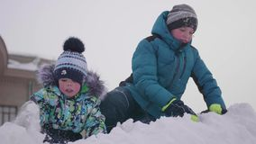 Dzieci bawić się na śnieżnej górze, rzucający śnieg i smejutsja Pogodny mroźny dzień Zabawa i gry w świeżym powietrzu