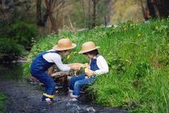 Dzieci, bawić się na małej rzece z kaczątkami Obrazy Royalty Free