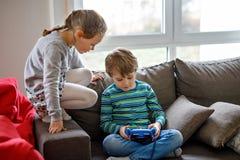 Dzieci bawić się na pastylce Dzieciaki patrzeje gadżet Obraz Stock
