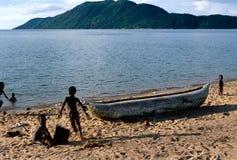 Dzieci bawić się obok pirogue, Jeziorny Malawi. Obrazy Stock