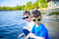 Dzieci bawić się outdoors w naturze: siedzieć na jeziornego, rzecznego brzeg wzruszającym piasku w jasnej wodzie na ciepłym dniu  fotografia royalty free