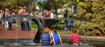 Dzieci bawić się pod wielorybią ogon fontanną Zdjęcia Stock