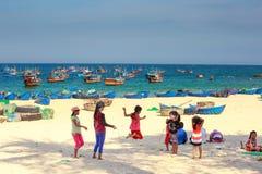 Dzieci bawić się skok arkanę na piaskowatym wybrzeżu wioska rybacka Obrazy Royalty Free