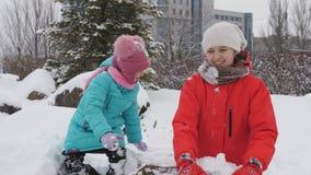 Dzieci bawić się snowballs w zimie Dwa siostry pleśnieją snowballs i rzucają przy twój przyjaciółmi zdjęcie wideo