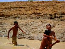 Dzieci bawić się w błotnistym nawadniają Obraz Royalty Free