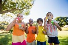 Dzieci bawić się z bąbel różdżką w parku Fotografia Royalty Free