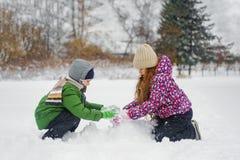 Dzieci bawić się z bałwanem na zimie chodzą w parku obrazy stock