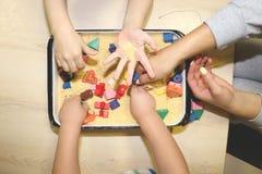 Dzieci bawić się z kinetycznym piaskiem, dławem i projektantem w preschool, Rozwój grzywny silnika pojęcie Twórczości gra fotografia royalty free