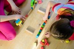 Dzieci bawić się z kolorowymi drewnianymi blokami fotografia royalty free