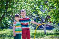 Dzieci bawi? si? z ogrodowym kropid?em Preschooler ?artuje bieg i skok Lato plenerowa wodna zabawa w podw?rku fotografia royalty free
