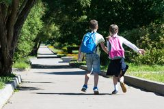 Dzieci biegali zdala od szkoły z lekcjami w dobrej pogodzie obraz royalty free