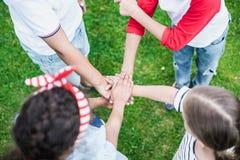 Dzieci broguje ręki podczas gdy stojący na zielonej trawie Obrazy Stock