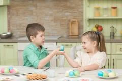 Dzieci chłopiec i dziewczyna bawić się z Wielkanocnymi jajkami i śmiechem Zdjęcie Royalty Free