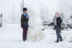 Dzieci chłopiec outdoors i dziewczyna w śnieżnej zimie robią dużemu Obrazy Stock