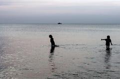 Dzieci chodzą na plaży w spokojnym morzu i emocjonalnie opowiadają sylwetki Fotografia Stock