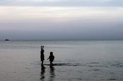 Dzieci chodzą na plaży w spokojnym morzu i emocjonalnie opowiadają sylwetki Fotografia Royalty Free