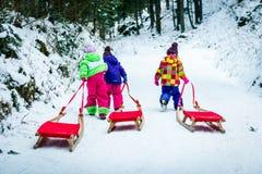 Dzieci ciągną saneczki na halnej drodze w drewnach Obrazy Stock