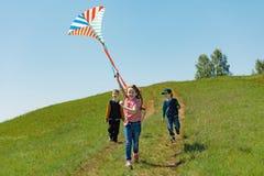 Dzieci cieszą się bawić się z latającą kanią w łące na słonecznym dniu Zdjęcia Stock