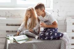 Dzieci czyta książkę i pije mleko Zdjęcie Royalty Free