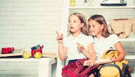 Dzieci czyta od ksi??ek wp?lnie podczas gdy siedz?cy puszek obrazy royalty free