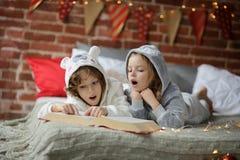 Dzieci czytają wielką książkę z Bożenarodzeniowymi bajkami Obrazy Stock