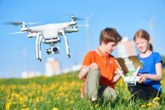 Dzieci działać latający truteń przy zmierzchem fotografia stock