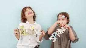 Dzieci gratulują na wakacje wiosna Dziewczyna i chłopiec chwyta znaki z inskrypcjami powitanie i wiosna zbiory wideo