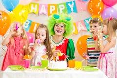 Dzieci i błazen przy przyjęciem urodzinowym obraz royalty free