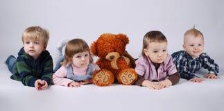 Dzieci i czerwień niedźwiedź na jaskrawym tle Obrazy Stock