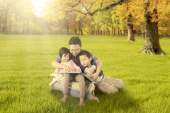 Dzieci i tata czyta książkę przy jesień parkiem Fotografia Royalty Free
