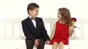 Dzieci jadą huśtawkę i troszkę całuje dziewczyny na policzku chłopiec Biały tło zbiory