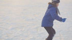 Dzieci jeździć na łyżwach na lodowym lodowisku przeciw zmierzchowi nad zima park zbiory wideo