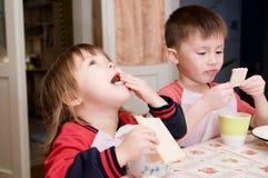 Dzieci je lunch, zdrowego karmowego pojęcie w domu, dzieciaki cieszy się chleb i jogurt, rodzeństwo emocjonalne twarze, zdrowy śn Obrazy Royalty Free