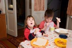 Dzieci je lunch, zdrowego karmowego pojęcie w domu, dzieciaki cieszy się chleb i jogurt, rodzeństwo emocjonalnie stawiają czoło Obraz Stock