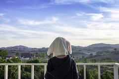 Dzieci jest ubranym zima kapelusz Na balkonie przegapia i żakiet góry i niebo obrazy stock