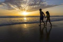 Dzieci kąpać się na plaży przy półmrokiem zdjęcia royalty free