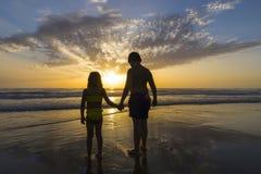 Dzieci kąpać się na plaży przy półmrokiem obrazy royalty free