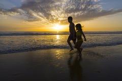 Dzieci kąpać się na plaży przy półmrokiem fotografia royalty free