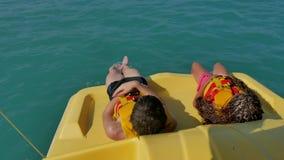 Dzieci kłamają odpoczywać na jachtu łódkowatym dennym oceanie dzieciaki jadą catamaran łódź w oceanie na wodzie zbiory wideo
