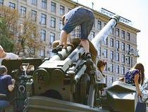 Dzieci które bawić się militarnego wyposażenie podczas wystawy w Kijów Wrzesień 23, 2017 Obraz Royalty Free