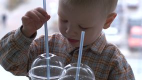 Dzieci lunch w fast food kawiarni Chłopiec piją lemoniadę i jedzą hamburgery w tle parking i pejzaż miejski zbiory