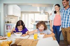 Dzieci ma śniadanie podczas gdy rodzice stoi stołem Zdjęcia Royalty Free