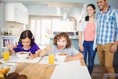 Dzieci ma śniadanie podczas gdy szczęśliwi rodzice stoi stołem Obrazy Stock