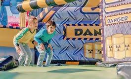 Dzieci ma zabawę przy parkiem rozrywki Przejażdżka na czółnie szczęśliwy dzieciństwa pojęcie obraz stock