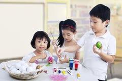 Dzieci maluje Easter jajka fotografia royalty free