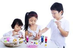 Dzieci maluje Easter jajka obraz royalty free