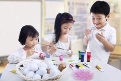 Dzieci maluje jajka Obrazy Stock